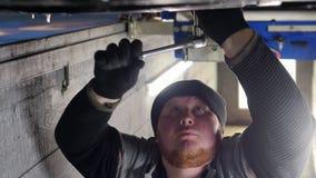 Servizio dell'automobile Condizione spessa dell'uomo del meccanico nel pozzo di ispezione sotto l'automobile e lavorare con uno s stock footage