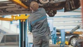 Servizio dell'automobile - meccanico che avvolge dispositivo funzionante nell'ambito del fondo dell'automobile fotografia stock libera da diritti