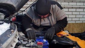 Servizio dell'automobile Misura spessa dell'uomo del meccanico la batteria stock footage