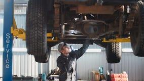 Servizio dell'automobile - un meccanico controlla la sospensione di SUV, grandangolare immagini stock