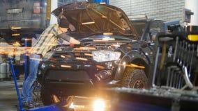 Servizio dell'automobile Uomo del meccanico che fa una pausa l'automobile con il cappuccio aperto e che lavora con uno strumento  fotografie stock libere da diritti