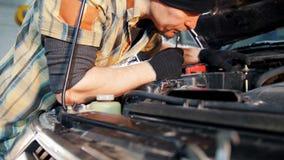Servizio dell'automobile Uomo del meccanico che ripara un'automobile con una chiave archivi video