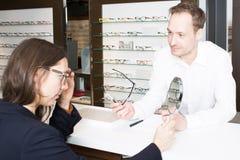Servizio di assistenza al cliente quando i vetri d'acquisto in un ottico comperano immagine stock libera da diritti