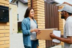 Servizio di distribuzione Donna di Delivering Package To del corriere a casa fotografia stock