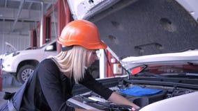 Servizio di riparazione dell'automobile, giovane donna in cappuccio dell'automobile di apertura del casco ed interno di sguardo stock footage