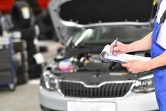 Servizio ed ispezione di un'automobile in un'officina - il meccanico ispeziona immagini stock