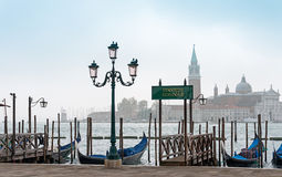 Servizio gondole. Venetian gondolas on the waterside of lagoon Royalty Free Stock Photography