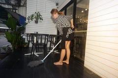 Servizio sorridente di pulizia della domestica femminile asiatica con il pavimento di pulizia di zazzera sul negozio fotografia stock libera da diritti