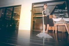 Servizio sorridente di pulizia della domestica femminile asiatica con il pavimento di pulizia di zazzera sul negozio immagini stock