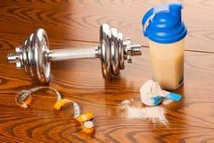 Serwatki proteiny proszek w miarce, dumbbell, metrowej taśmie s i klingerycie, zdjęcie royalty free