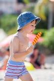 Süßes kleines Kind, Junge, Eiscreme auf dem Strand essend Stockfotografie