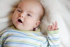 Süßes kleines neugeborenes Schätzchen in einem Bett Stockbilder