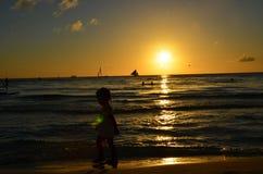 Süßes Mädchenschattenbild, das zu den Wellen gegen den Sonnenuntergang neigt Lizenzfreies Stockfoto