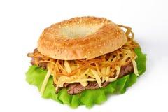Sesam bagel med cirklar för grillat nötkött, för grön sallad, ost- och lök Royaltyfria Bilder
