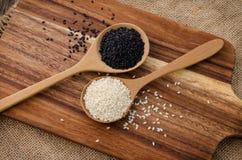 Sesam zwart-wit in houten lepel op Houten achtergrond Stock Foto's