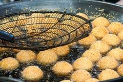 Sesamballen die in hete olie braden Stock Afbeeldingen