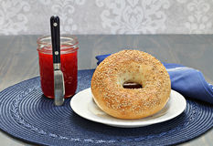 Sesame bagel with a jar of homemade strawberry jam. A sesame bagel with a jar of homemade strawberry jam preserves Stock Image