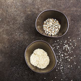 Sesame black, brown and white in dark ceramic bowls on a dark background. Top View.  Stock Images