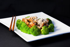 Sesame chicken. With broccolis and chopsticks Royalty Free Stock Images