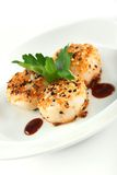 Sesame ginger scallop with hoisin sauce. Scallop seared with sesame seeds and ginger with hoisin sauce, garnished with parsley royalty free stock photos