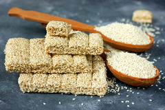 Sesame kozinaki and sesame seeds in wooden spoon Stock Photos