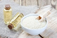 Sesame oil in a glass bottle and seeds royalty free stock photography