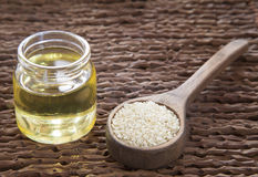 Sesame oil in glass jar and sesame seeds on wooden spoon - Sesamum indicum Royalty Free Stock Photos