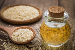 Sesame oil in glass jar and sesame seeds on wooden spoon Royalty Free Stock Images