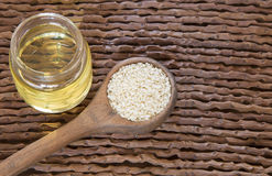 Sesame oil in glass jar and sesame seeds on wooden spoon - Sesamum indicum Stock Photos