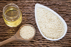 Sesame oil in glass jar and sesame seeds on wooden spoon - Sesamum indicum Royalty Free Stock Photography