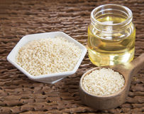 Sesame oil in glass jar and sesame seeds on wooden spoon - Sesamum indicum Royalty Free Stock Images