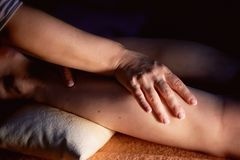 Sesame oil massage for calf muscle. Relaxation treatment for young female, close up. Sports massage -Leg massage - stock image