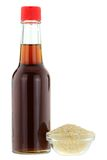 Sesame oil next to a bowl of white Sesame seeds Royalty Free Stock Photography