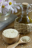Sesame. Seed in a wooden bowl against flowers and a bottle with  oil. Useful product with the content of calcium and antioxidants Stock Photography