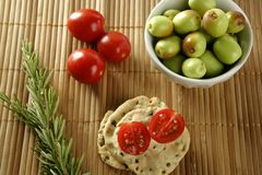 Sesame seeds biscuits with tomato. Sesame seeds biscuits over bamboo stripes, tomatoes ans rosemery royalty free stock images