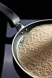 Sesame seeds in black frying pan Stock Image