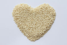 Sesame seeds in the form of heart. On a white background Royalty Free Stock Photo
