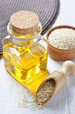 Sesame seeds and oil. In a glass bottle on a wooden background Stock Photo