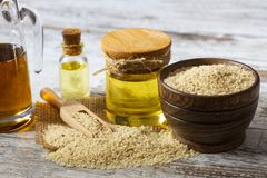 Sesame seeds in sack and bottle of oil on wooden rustic table royalty free stock photo