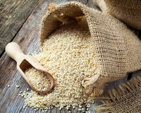 Sesame seeds in sack on  rustic table Royalty Free Stock Photos