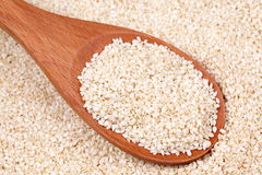 Sesame seeds in a wooden spoon. On seasame seed background. Close-up Stock Photo