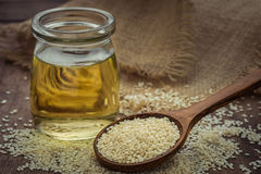 Sesame seeds on wooden spoon and sesame oil in glass jar Royalty Free Stock Photography