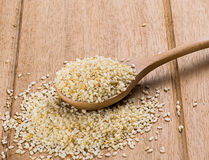 Sesame seeds with wooden spoon. On wood background stock photo