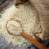 Sesame seeds in wooden spoon on wooden rustic table royalty free stock image