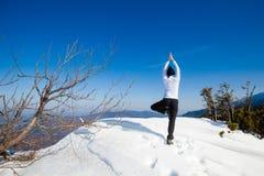 Sesión de la yoga del invierno en lugar hermoso de la montaña Fotos de archivo libres de regalías