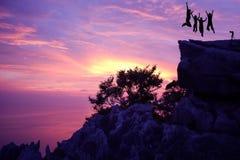 Sesión fotográfica y salto de la familia en la montaña Imagenes de archivo