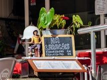 SESIMBRA PORTUGAL - CIRCA MAJ 2017: Restaurangtecknet som säger ` har vi, snigel` i strandstaden av Sesimbra, Portugal arkivfoton
