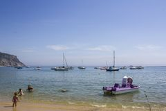 Scenic beach with recreation boats and people on water. SESIMBRA, PORTUGAL - CIRCA SEPTEMBER, 2018: Scenic beach with stock images