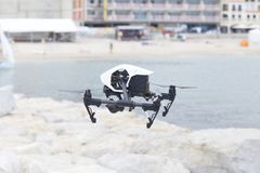 White quadcopter drone. Sesimbra, Portugal, July 11, 2018. White quadcopter drone with photo camera over the sea. Close-up on a white quadcopter drone. This kind stock image