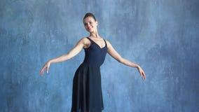 Sesja Zdjęciowa. Dziewczyna w pointes tanczy na szarym tle wewnątrz zdjęcie wideo
